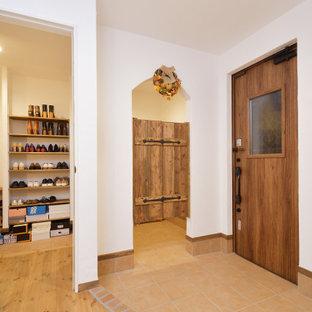 Réalisation d'une grand porte d'entrée style shabby chic avec un mur blanc, un sol en bois brun, une porte simple, une porte en bois brun et un sol marron.
