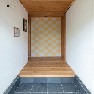 神戸の北欧スタイルのおしゃれな玄関ホール (白い壁、黒い床) の写真