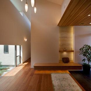 他の地域の片開きドアモダンスタイルのおしゃれな玄関ホール (白い壁、無垢フローリング、木目調のドア、茶色い床) の写真