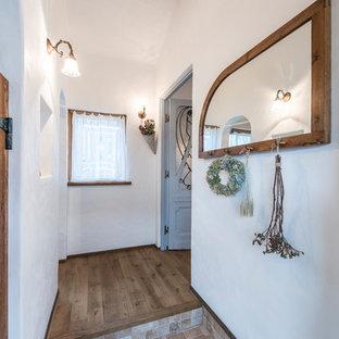 福岡の中くらいの片開きドア地中海スタイルのおしゃれな玄関ホール (白い壁、淡色無垢フローリング、茶色いドア、茶色い床) の写真