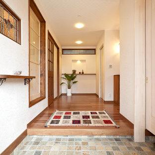 他の地域の地中海スタイルのおしゃれな玄関ホール (白い壁、茶色い床、大理石の床、茶色いドア) の写真