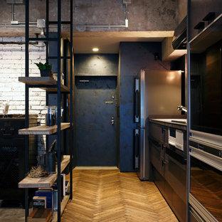 Industriell inredning av en hall, med grå väggar, mellanmörkt trägolv, en enkeldörr och en svart dörr
