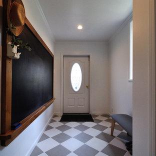 他の地域の片開きドアヴィクトリアン調のおしゃれな玄関ホール (白い壁、白いドア、マルチカラーの床) の写真