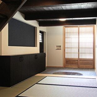 Неиссякаемый источник вдохновения для домашнего уюта: огромная узкая прихожая в восточном стиле с белыми стенами, татами и входной дверью из дерева среднего тона