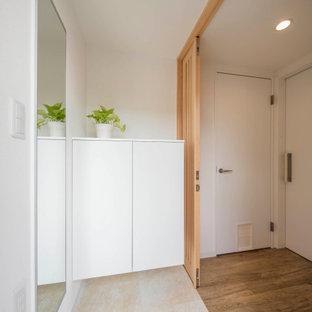 Foto på en mellanstor minimalistisk hall, med vita väggar, klinkergolv i keramik, en enkeldörr, en grå dörr och vitt golv