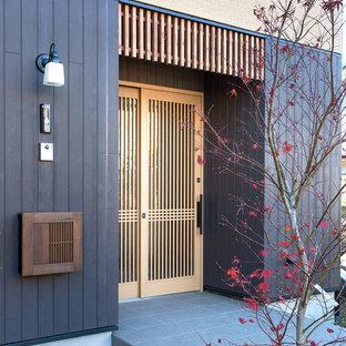 他の地域の片開きドアアジアンスタイルのおしゃれな玄関ドア (黒い壁、淡色木目調のドア、グレーの床) の写真