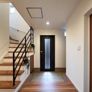他の地域の片開きドアモダンスタイルのおしゃれな玄関ホール (白い壁、濃色木目調のドア) の写真