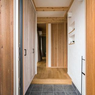 他の地域の小さい片開きドアカントリー風おしゃれな玄関 (白い壁、グレーの床、セラミックタイルの床、木目調のドア) の写真