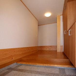 Свежая идея для дизайна: маленькая узкая прихожая в стиле модернизм с белыми стенами, полом из фанеры и коричневым полом - отличное фото интерьера