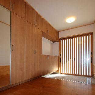 Cette image montre une petit entrée minimaliste avec un couloir, un mur blanc, un sol en contreplaqué, une porte coulissante, une porte en bois brun et un sol marron.