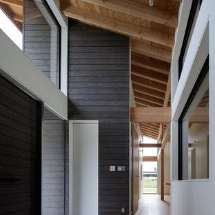 他の地域の中くらいの両開きドアコンテンポラリースタイルのおしゃれな玄関ホール (白い壁、グレーのドア、淡色無垢フローリング、ベージュの床) の写真
