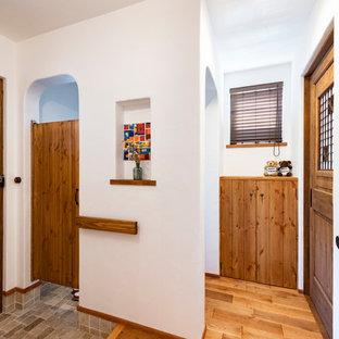 他の地域の中くらいの片開きドアカントリー風おしゃれな玄関ホール (白い壁、濃色無垢フローリング、木目調のドア、茶色い床) の写真