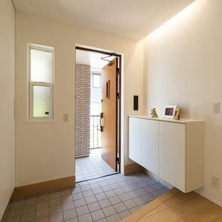 他の地域, の片開きドアアジアンスタイルのおしゃれな玄関ホール (白い壁、木目調のドア、グレーの床) の写真