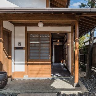 他の地域の引き戸和風のおしゃれな玄関 (白い壁、木目調のドア、グレーの床) の写真