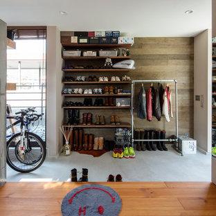 他の地域のラスティックスタイルのおしゃれな玄関 (濃色木目調のドア、マルチカラーの壁、コンクリートの床、グレーの床) の写真