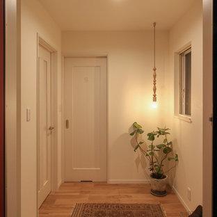 他の地域のおしゃれな玄関ホール (白い壁、淡色無垢フローリング、ベージュの床) の写真