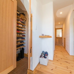 Mudroom - asian brown floor mudroom idea in Other with white walls