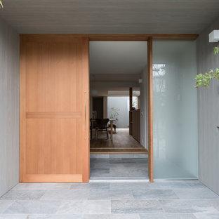 Inredning av en modern ingång och ytterdörr, med grå väggar, kalkstensgolv, en skjutdörr och ljus trädörr