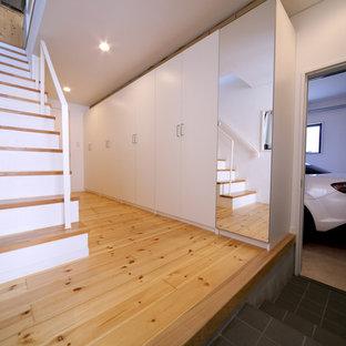 Bild på en liten funkis hall, med vita väggar, plywoodgolv, en enkeldörr, en svart dörr och beiget golv