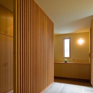 Выдающиеся фото от архитекторов и дизайнеров интерьера: узкая прихожая в восточном стиле с бежевыми стенами, паркетным полом среднего тона и бежевым полом