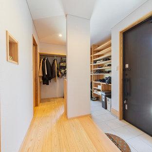 他の地域の片開きドアモダンスタイルのおしゃれな玄関 (白い壁、黒いドア) の写真