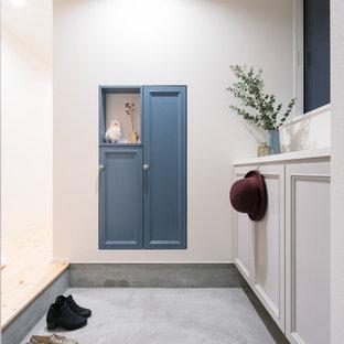 他の地域の北欧スタイルのおしゃれな玄関ホール (白い壁、コンクリートの床、グレーの床) の写真
