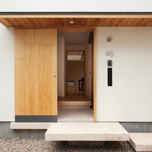 Новые идеи обустройства дома: входная дверь в восточном стиле с белыми стенами, бетонным полом, раздвижной входной дверью и входной дверью из светлого дерева