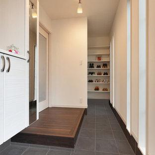 Inspiration pour une entrée minimaliste avec un couloir, un mur blanc, un sol en contreplaqué et un sol marron.
