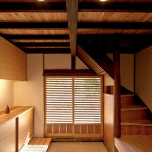 Idee per un ingresso o corridoio etnico con pareti bianche, una porta scorrevole, una porta in legno bruno e pavimento beige