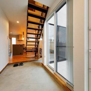 Foto på ett mellanstort industriellt kapprum, med vita väggar, plywoodgolv, en enkeldörr, en svart dörr och grått golv