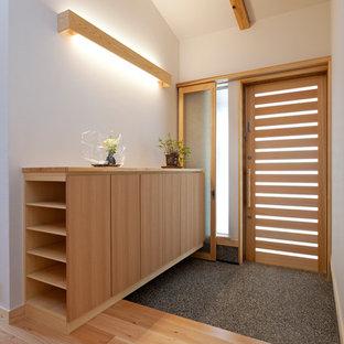 Идея дизайна: маленькая узкая прихожая в восточном стиле с белыми стенами, светлым паркетным полом, раздвижной входной дверью, входной дверью из светлого дерева и бежевым полом