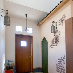 他の地域の片開きドア和風のおしゃれな玄関ホール (白い壁、コンクリートの床、木目調のドア、グレーの床) の写真