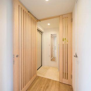 Réalisation d'une entrée nordique de taille moyenne avec un couloir, un mur blanc, béton au sol, une porte simple, une porte en bois brun, un sol gris, un plafond en papier peint et du papier peint.