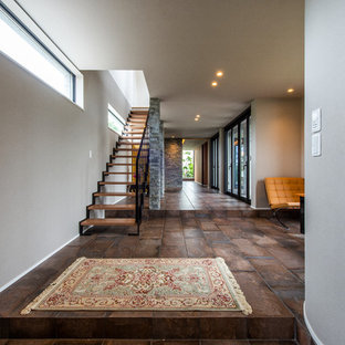 他の地域の広い両開きドアアジアンスタイルのおしゃれな玄関ホール (グレーの壁、磁器タイルの床、濃色木目調のドア、茶色い床) の写真