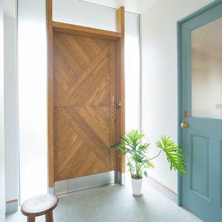 Ejemplo de hall romántico, de tamaño medio, con paredes blancas, suelo de cemento, puerta simple, puerta de madera en tonos medios y suelo gris