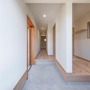 Cette image montre une entrée asiatique avec un couloir, un mur blanc, béton au sol, une porte simple, une porte en bois brun, un sol gris, un plafond en papier peint et du papier peint.
