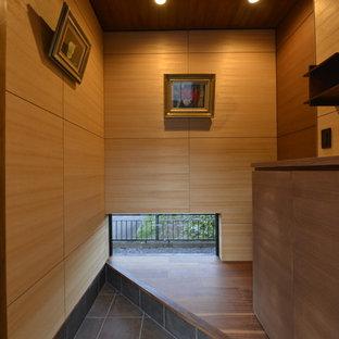 東京23区の和風のおしゃれな玄関 (茶色い壁、黒い床) の写真