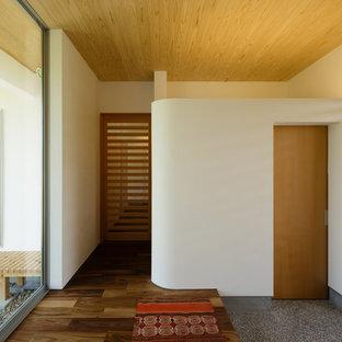 Diseño de entrada actual con paredes blancas, suelo de madera en tonos medios y suelo marrón