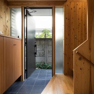 東京23区の中くらいの片開きドア和風のおしゃれな玄関ドア (茶色い壁、磁器タイルの床、濃色木目調のドア、グレーの床) の写真