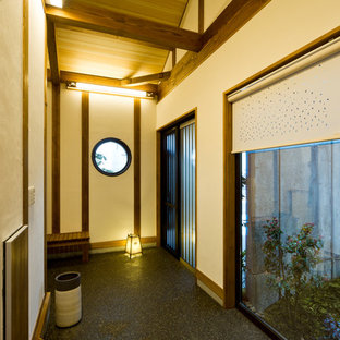 Photo of a world-inspired entrance in Other with beige walls, a sliding front door and black floors.