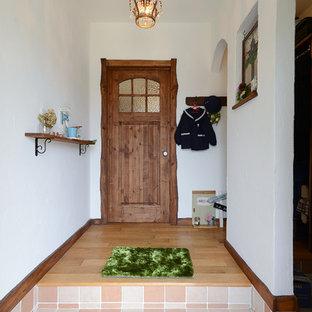 他の地域の片開きドア地中海スタイルのおしゃれな玄関ホール (白い壁、濃色木目調のドア、オレンジの床) の写真