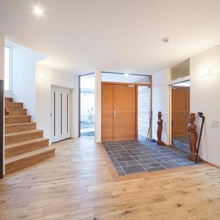 他の地域のアジアンスタイルのおしゃれな玄関 (白い壁、茶色いドア、茶色い床) の写真