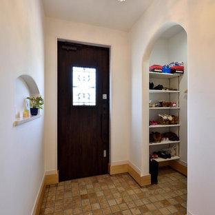 他の地域の片開きドア地中海スタイルのおしゃれな玄関 (白い壁、濃色木目調のドア、茶色い床) の写真