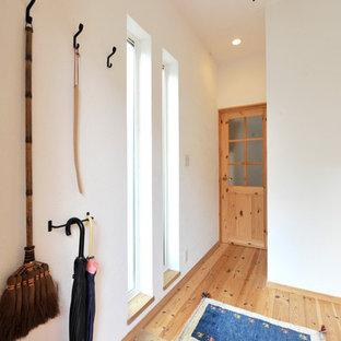 他の地域のモダンスタイルのおしゃれな玄関 (白い壁、テラコッタタイルの床、オレンジの床) の写真