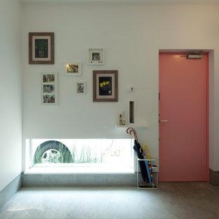 横浜の中サイズの片開きドアモダンスタイルのおしゃれな玄関ホール (グレーの壁、コンクリートの床、赤いドア、グレーの床) の写真