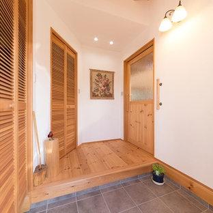 他の地域の引き戸アジアンスタイルのおしゃれな玄関 (白い壁、グレーの床、黒いドア) の写真