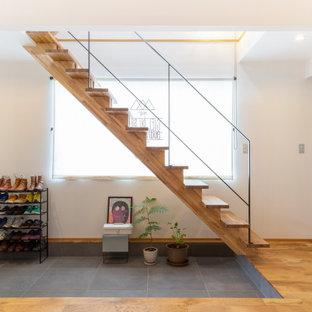 他の地域の広い片開きドアアジアンスタイルのおしゃれな玄関ロビー (白い壁、無垢フローリング、黒いドア、ベージュの床) の写真