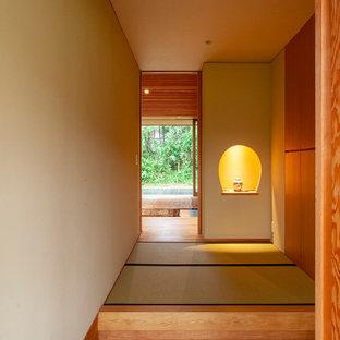 Foto på en mellanstor orientalisk hall, med vita väggar, tatamigolv, en enkeldörr, mörk trädörr och beiget golv