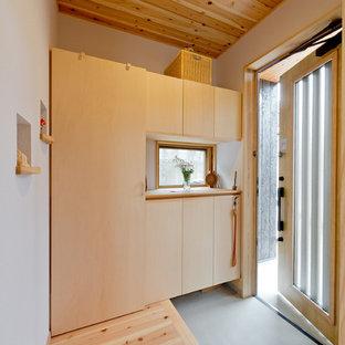 神戸の片開きドアアジアンスタイルのおしゃれな玄関 (白い壁、グレーの床) の写真