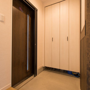 Inspiration för små asiatiska hallar, med vita väggar, betonggolv, en skjutdörr, mörk trädörr och grått golv